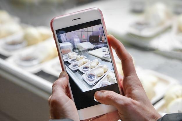 La donna sta prendendo foto mobile di preparazione del cibo in un ristorante