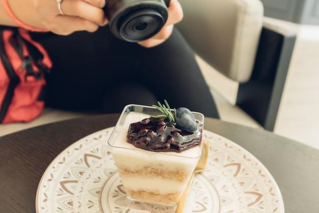 La donna sta prendendo una foto della sua cheesecake ai mirtilli.