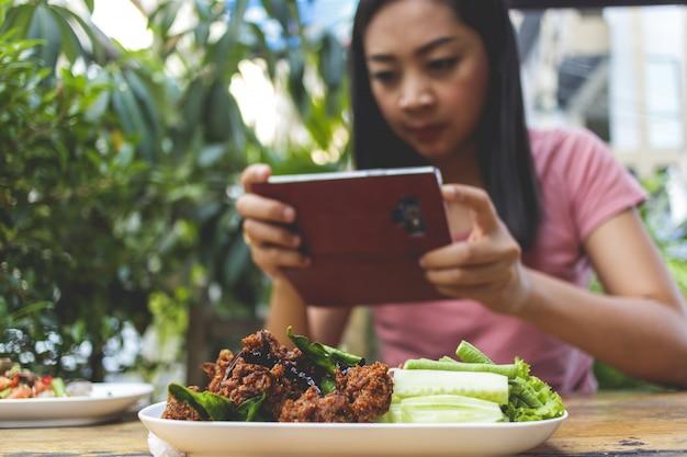 La donna sta prendendo una foto di cibo tailandese sul tavolo.