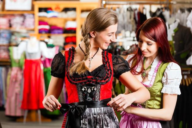 La donna sta provando tracht o il dirndl in un negozio