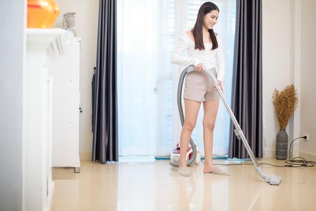 La donna sta pulendo casa con la macchina del vuoto