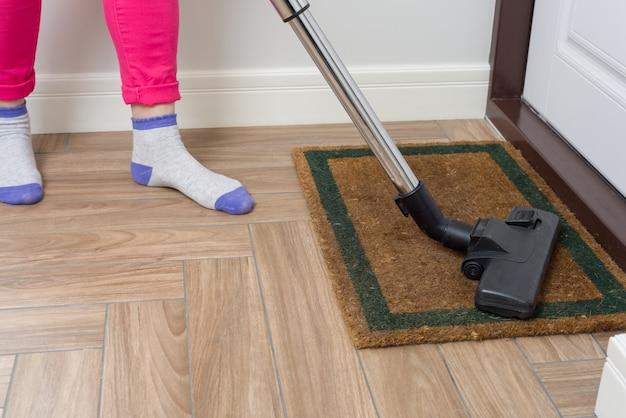 La donna sta pulendo usando l'aspirapolvere