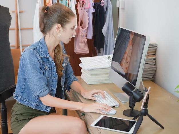 La donna sta rispondendo alle domande dei clienti attraverso il loro computer sulla vendita online, la ragazza fa affari a casa sua