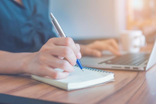 La donna sta scrivendo su un taccuino con una penna e sta usando un computer portatile per lavorare in ufficio.