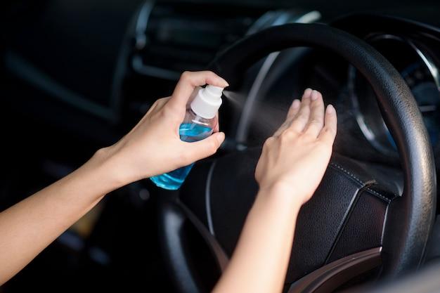 La donna sta spruzzando il disinfettante per le mani sulle sue mani in automobile