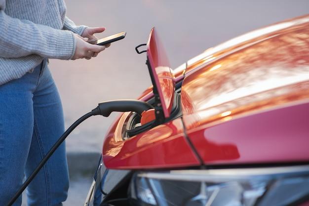 La donna sta tappando il veicolo elettrico per caricare la batteria dell'auto al parcheggio. avvicinamento. ricarica auto elettrica. auto ev collegata al caricabatterie