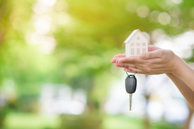 La donna sta tenendo la chiave dell'automobile e della casa su verde