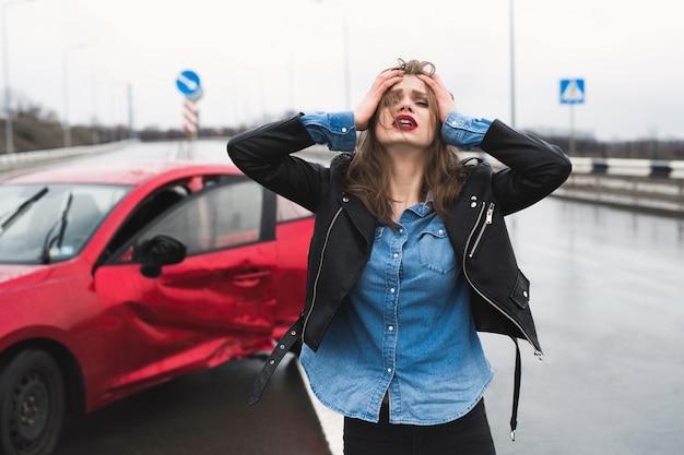 La donna sta vicino a un'auto rotta dopo un incidente