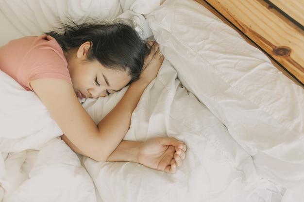 La donna stanca riposa e dorme nella sua camera da letto calda.