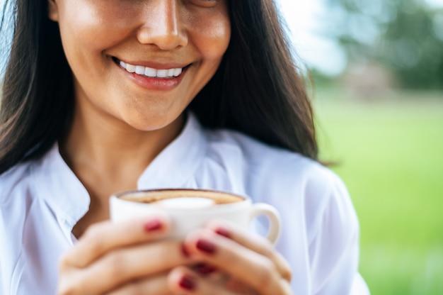 La donna stava felicemente a bere il caffè sul prato