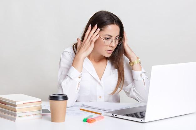 La donna stressante guarda con espressione perplessa sullo schermo, indossa una camicia formale, impegnata a redigere un rapporto finanziario, si sente preoccupata per le scadenze, sente mal di testa dal ricevere cattive notizie