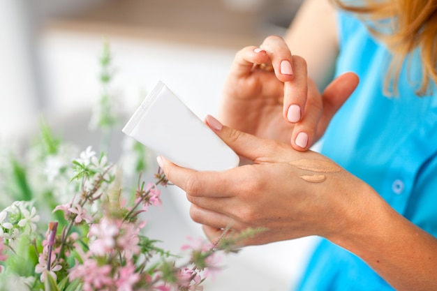 La donna strofina il liquido da un barattolo bianco sulla pelle con la mano