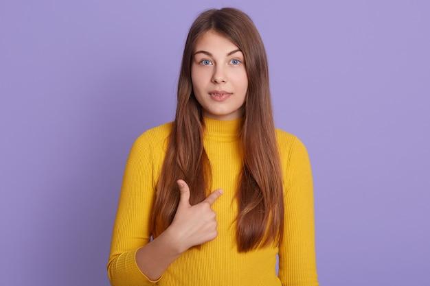La donna stupita con i capelli lunghi punta verso se stessa, indossa un maglione giallo, ha sorpreso l'espressione del viso, isolata sul muro lilla.