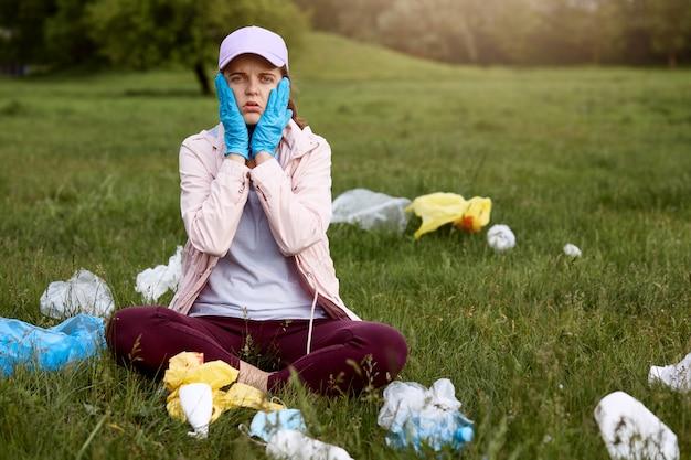 La donna stupita e scioccata seduta nel parco sull'erba verde con i palmi sulle guance, indossa casualmente, circondata dai rifiuti, ha bisogno di raccogliere tutta la spazzatura.