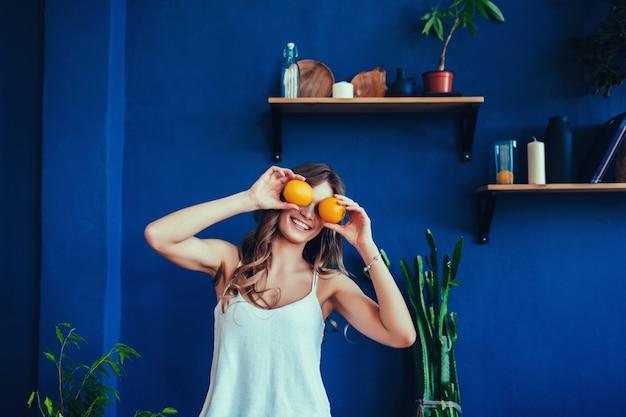La donna su una priorità bassa blu tiene un'arancia tagliata