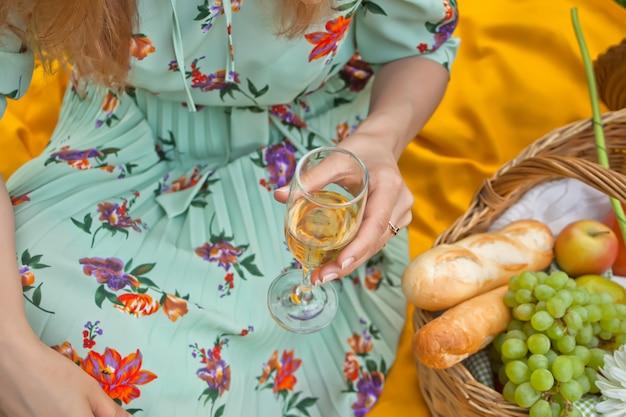La donna sul picnic si siede sulla copertina gialla e tiene il bicchiere di vino.