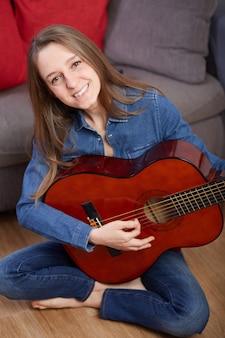 La donna suona la chitarra a casa