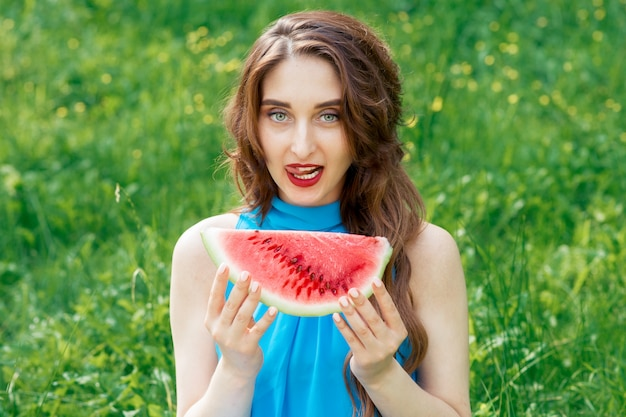 La donna sveglia piacevole attraente tiene il pezzo di anguria mentre mostra la lingua fuori.
