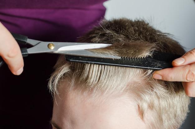 La donna taglia i capelli del ragazzo a casa. taglio di capelli fatto in casa