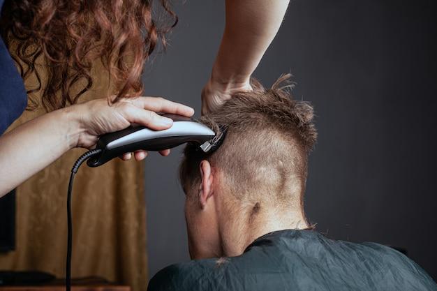 La donna taglia un uomo con un rifinitore in un parrucchiere. taglio di capelli alla moda.