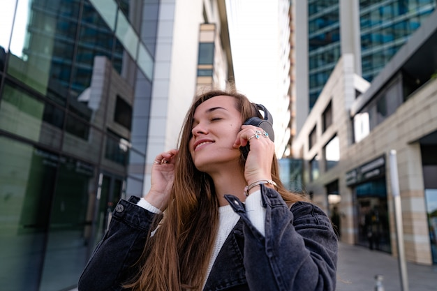 La donna teenager alla moda felice alla moda dei pantaloni a vita bassa teenager gode della musica in cuffie senza fili mentre cammina intorno alla città. amante della musica