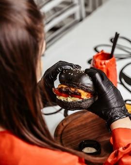 La donna tiene cheeseburger nero nelle mani