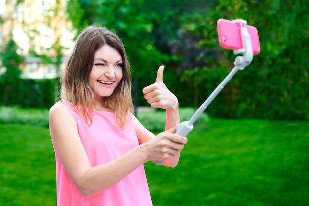 La donna tiene il bastone selfie con il cellulare con l'espressione del viso e invia selfie divertenti con il dito grosso ai parenti dalle vacanze