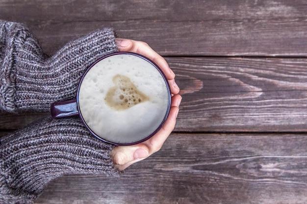 La donna tiene il latte caldo della tazza di caffè, il cappuccino con la crema del latte e cuore su fondo di legno, vista superiore
