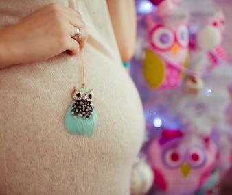 La donna tiene il piccolo gufo giocattolo sul ventre