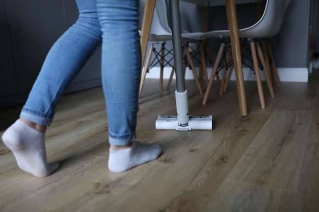 La donna tiene l'aspirapolvere bianco e lo guida attraverso il pavimento. servizi di concetto di imprese di pulizia.