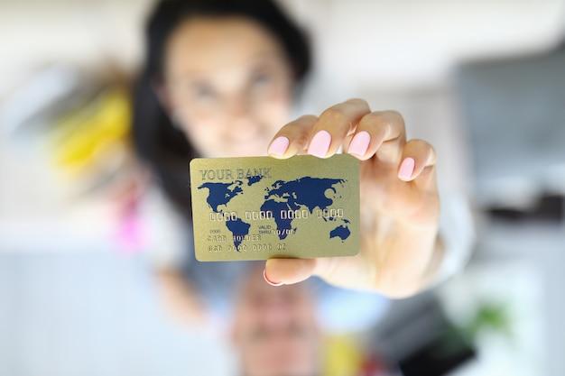 La donna tiene la carta di credito nel suo primo piano delle mani.