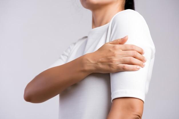 La donna tiene la ferita al braccio, sentendo dolore. assistenza sanitaria e concetto medico.
