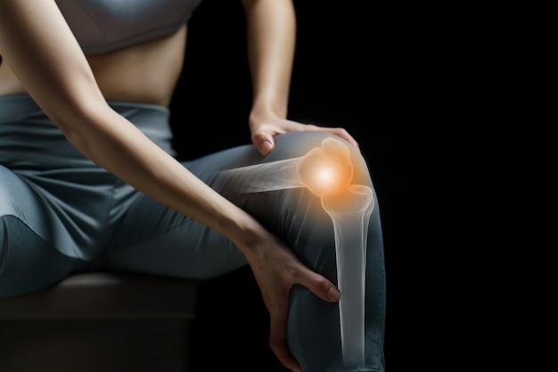 La donna tiene le mani al ginocchio, dolore al ginocchio evidenziato in rosso, medicina, concetto di massaggio.