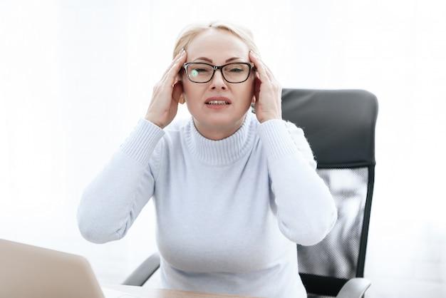La donna tiene le mani sulla testa. lei è seduta alla scrivania.