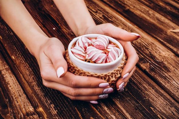 La donna tiene nelle sue mani tazza con cioccolate calde e marshmallow