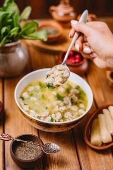 La donna tiene un cucchiaio di zuppa di gnocchi di dushbara servita con erbe e spezie essiccate
