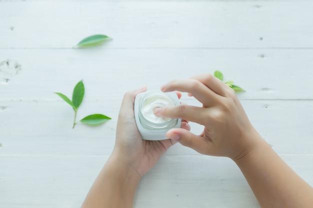 La donna tiene un vaso con una crema cosmetica nelle sue mani