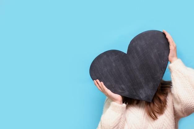 La donna tiene una lavagna a forma di cuore per san valentino