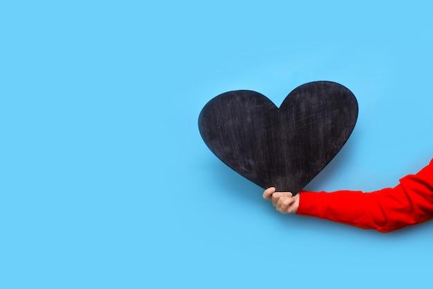 La donna tiene una lavagna a forma di cuore su uno sfondo blu per san valentino