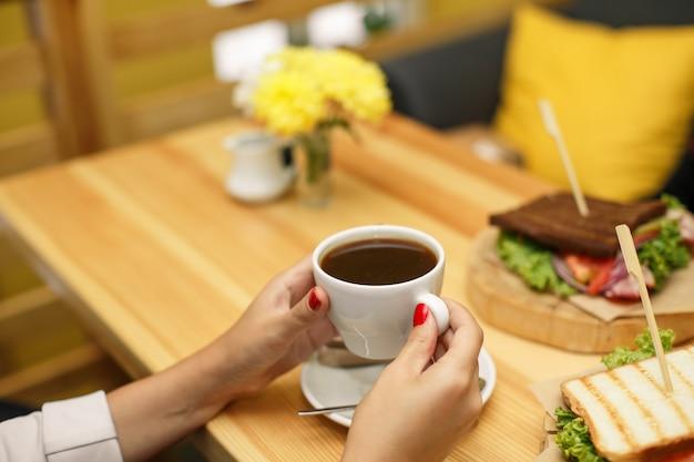 La donna tiene una tazza di caffè al tavolo di legno backgroud, su cui giace un panino