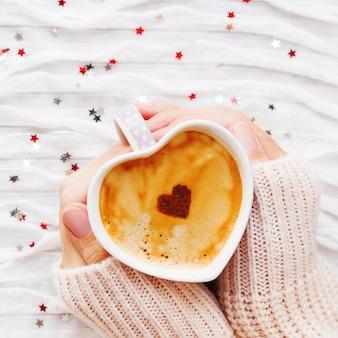 La donna tiene una tazza di caffè caldo con cuore di cannella