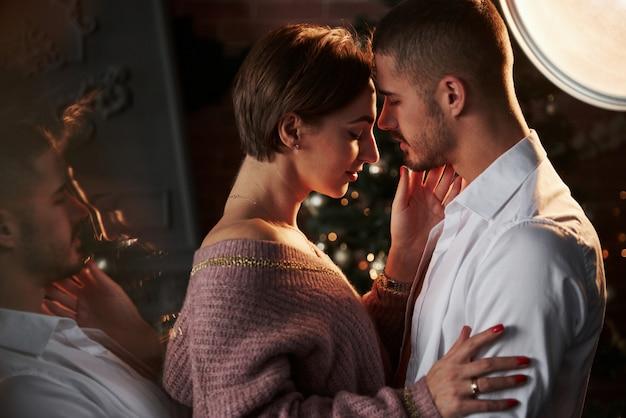 La donna tocca la barba a mano. la vicinanza del ragazzo e della ragazza in abiti di lusso che ballano e flirtano. splendido riflesso laterale