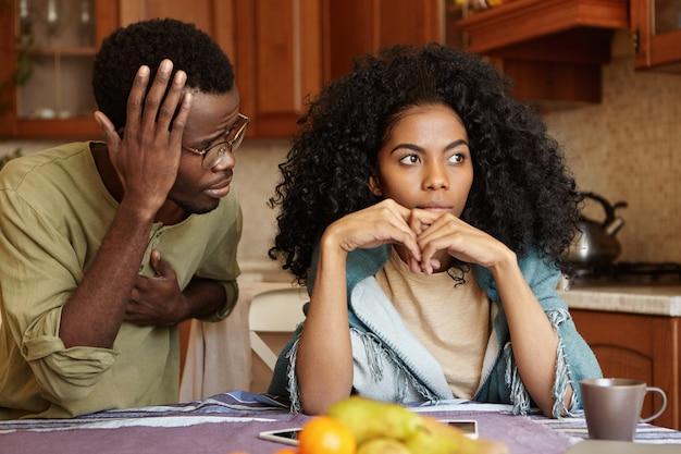 La donna triste e delusa non può perdonare il marito per infedeltà che è seduta accanto a lei con lo sguardo di scusa colpevole, dicendo che è stato un errore. coppie afroamericane che affrontano i problemi delle relazioni
