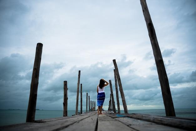 La donna triste e sola sta da sola su un ponte di legno sul mare.