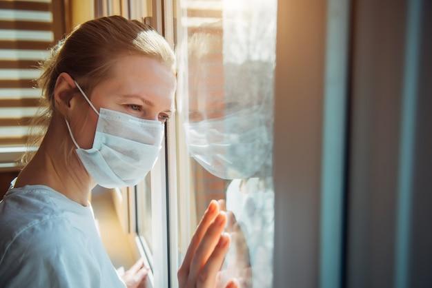 La donna triste in una mascherina medica protettiva guarda fuori dalla finestra