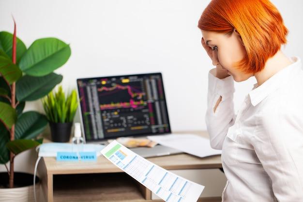 La donna triste sta guardando i grafici di borsa che cadono durante un'epidemia covid-19.