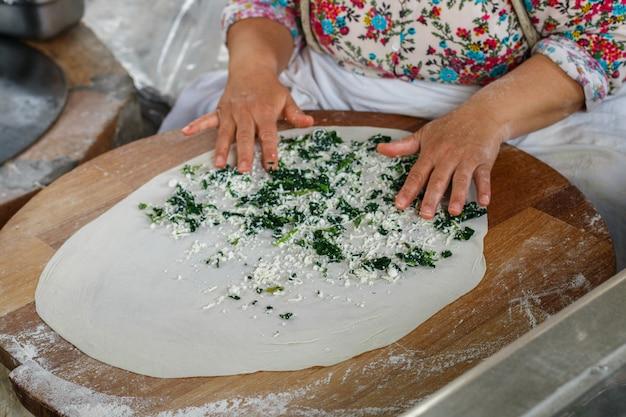 La donna turca prepara gozleme - piatto tradizionale a forma di focaccia farcita con verdure e formaggio