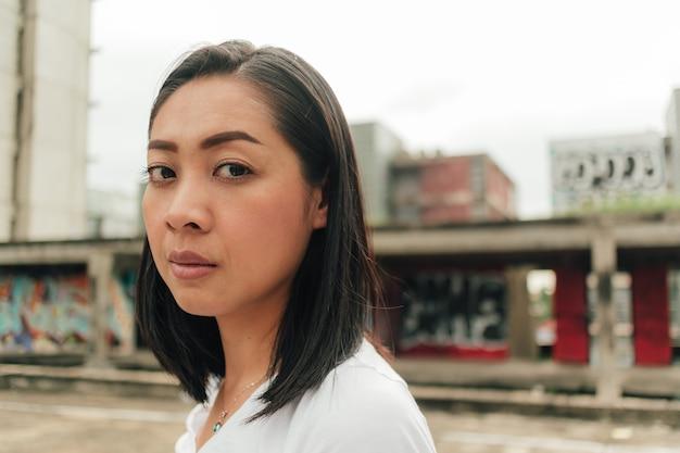 La donna turistica gode di esplorare un edificio abbandonato sconosciuto.