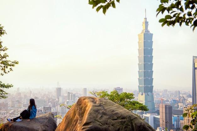 La donna turistica si siede sulla pietra gigante con 101 torre al tramonto