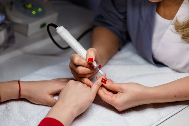 La donna usa la lima per unghie elettrica trapano nel salone di bellezza.